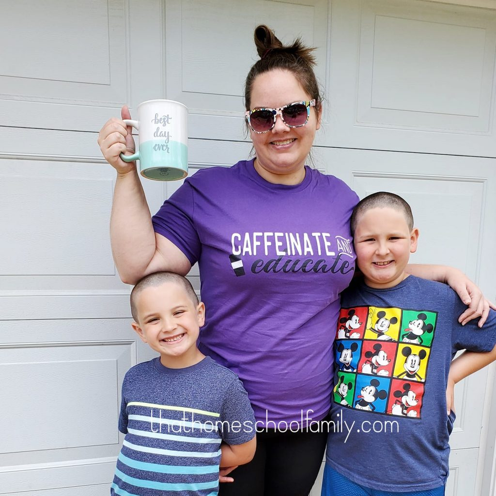 image of a mom holding a cup of coffee with two children on her side