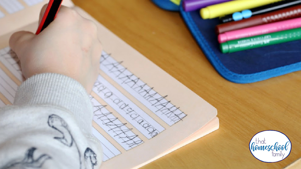 Image of a child practicing his handwriting and a set of markers nearby for the 4 Reasons Why We'll Continue Homeschooling After the Pandemic Ends article from That Homeschool Family written by Elizabeth Dukart