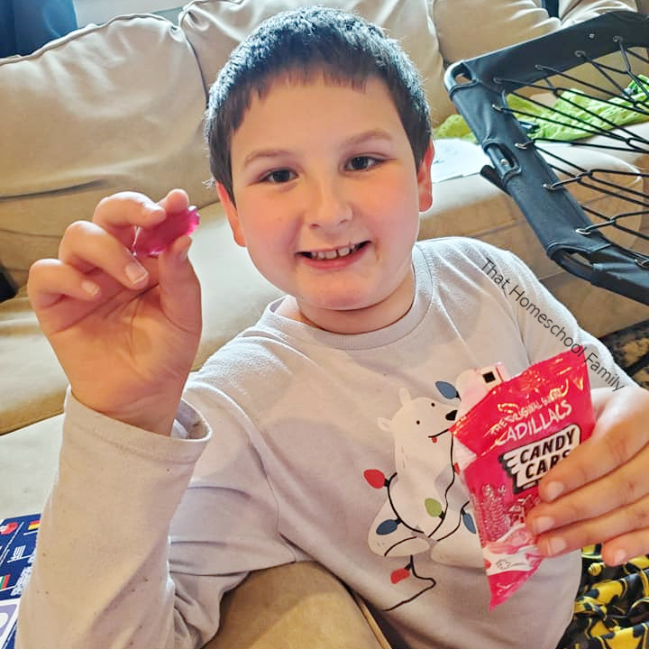 9 year old boy showing Cadillac Gummy Candies from our Universal Yums box from the Homeschool Geography is Delicious with Universal Yums article from That Homeschool Family written by Elizabeth Dukart