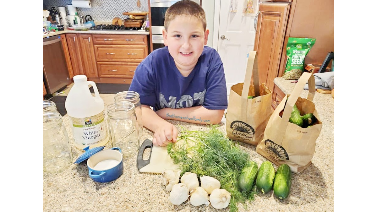 """image of a 9 year old boy in the kitchen with ingredients to make refrigerator pickles from the That Homeschool Family article """"Kids in the Kitchen: How to Make Refrigerator Pickles"""" written by Elizabeth Dukart"""