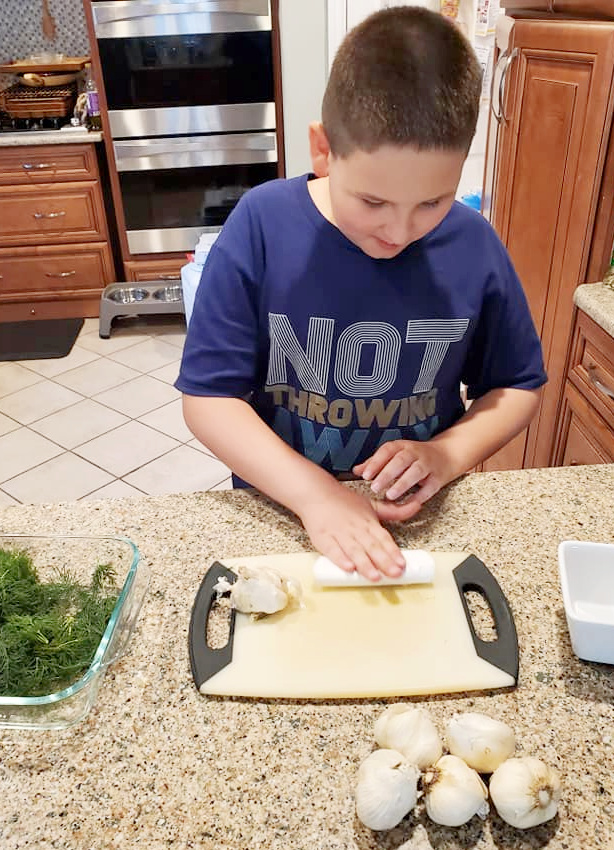 """image of 9 year old boy in a kitchen using a garlic peeler to peel the skin off a clove of garlic from the That Homeschool Family article """"Kids in the Kitchen: How to Make Refrigerator Pickles"""" written by Elizabeth Dukart"""