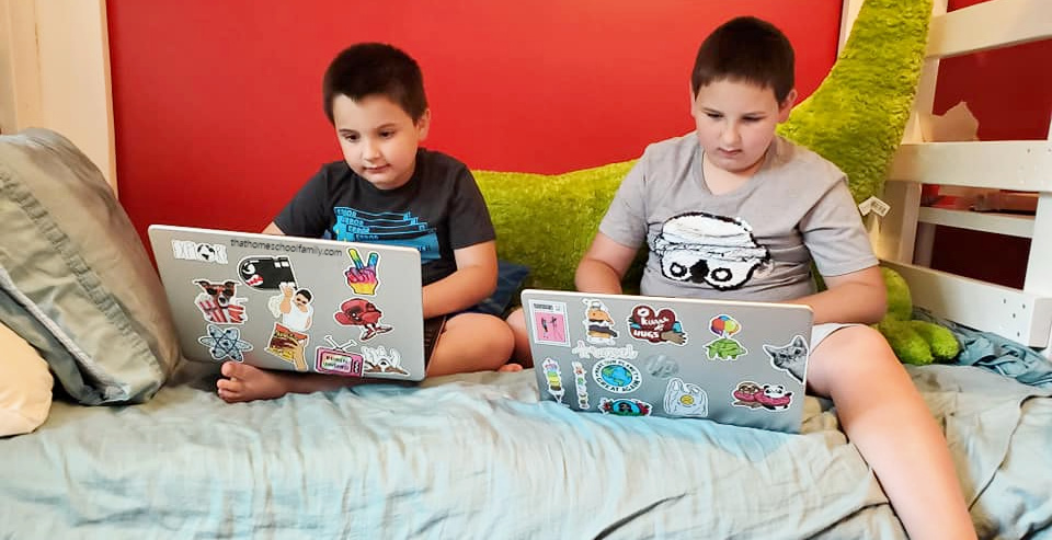 """two elementary age children sitting on the bottom bunk of a bunkbed each with their own laptop that's been decorated with stickers. From the article """"Using LightSail for Homeschoolers for Language Arts and Beyond"""" article from That Homeschool Family written by Elizabeth Dukart"""