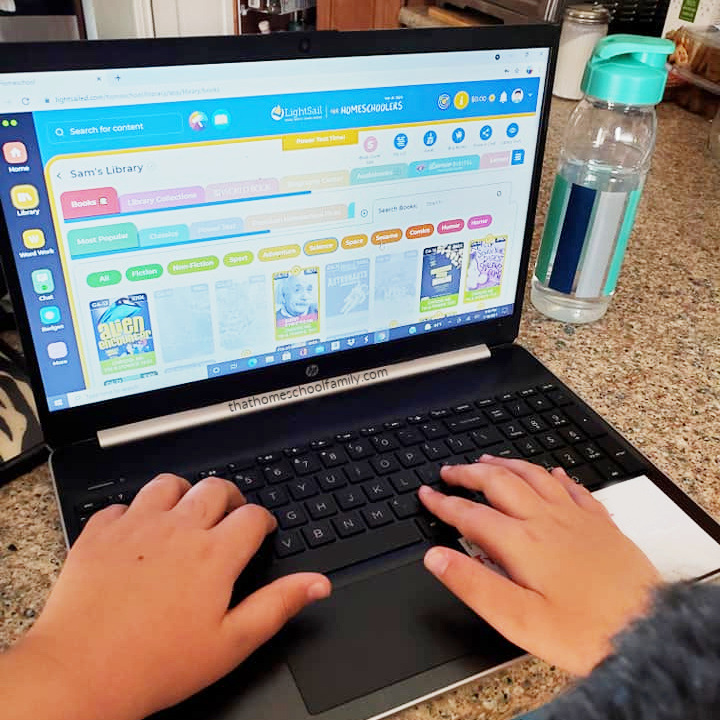"""a boy's hands on the keyboard of a laptop while sitting at the kitchen counter. Laptop is open to a page of the LightSail for Homeschoolers online platform. From the article """"Using LightSail for Homeschoolers for Language Arts and Beyond"""" from That Homeschool Family written by Elizabeth Dukart"""