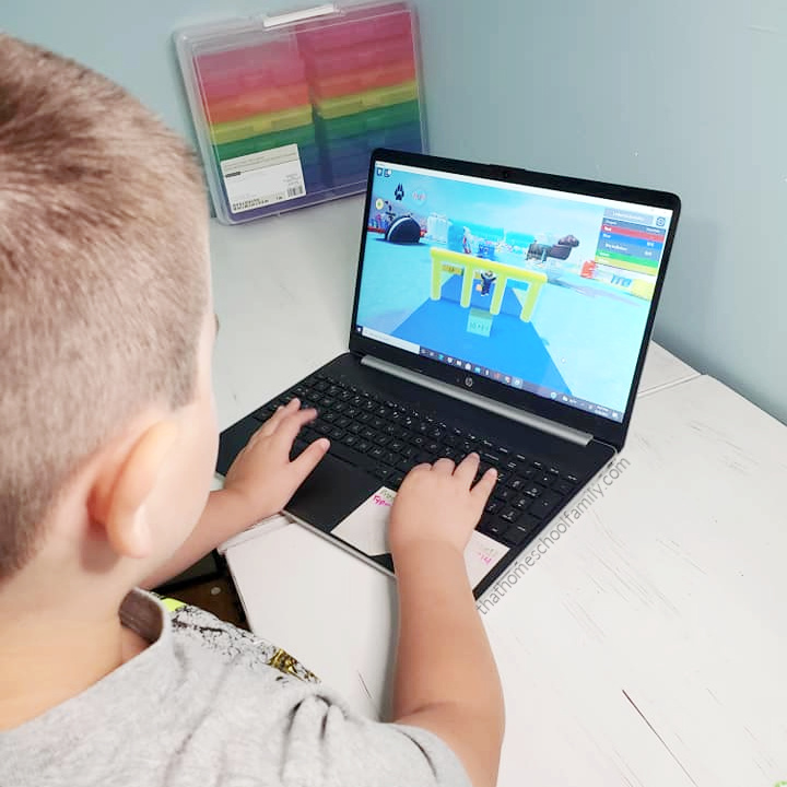"""7 year old boy playing educational games on a laptop computer through the Brainika Roblox game from the article """"Educational Games for Kids on Roblox"""" from That Homeschool Family written by Elizabeth Dukart"""