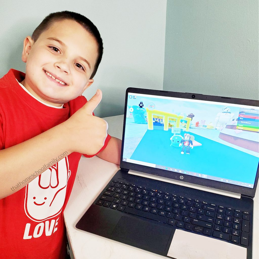 """7 year old boy in a red shirt giving the Brainika Roblox game a thumbs up from the article """"Educational Games for Kids on Roblox"""" from That Homeschool Family written by Elizabeth Dukart"""