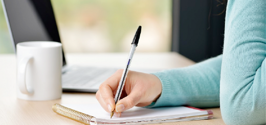 image of a woman writing a letter on a desk with a cup of coffee and laptop nearby for the article an open letter to parents considering homeschooling featured image That Homeschool Family written by Elizabeth Dukart