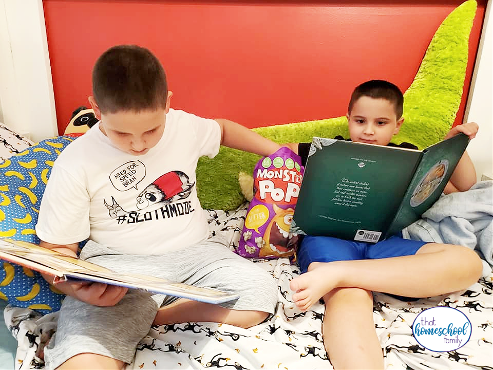 image of two elementary age boys reading books on a bed while eating Monster Pop Popcorn from the article Back to School Snacks with Monster Pop Popcorn from That Homeschool Family written by Elizabeth Dukart