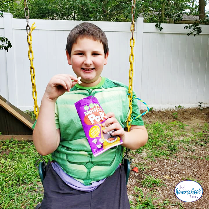 9 year old boy eating Monster Pop popcorn while sitting on a swing in the article Back to School Snacks with Monster Pop Popcorn from That Homeschool Family written by Elizabeth Dukart